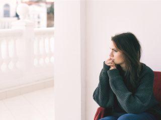 Eine imaginäre Frau sitzt in einem Sessel und schaut aus dem Fenster