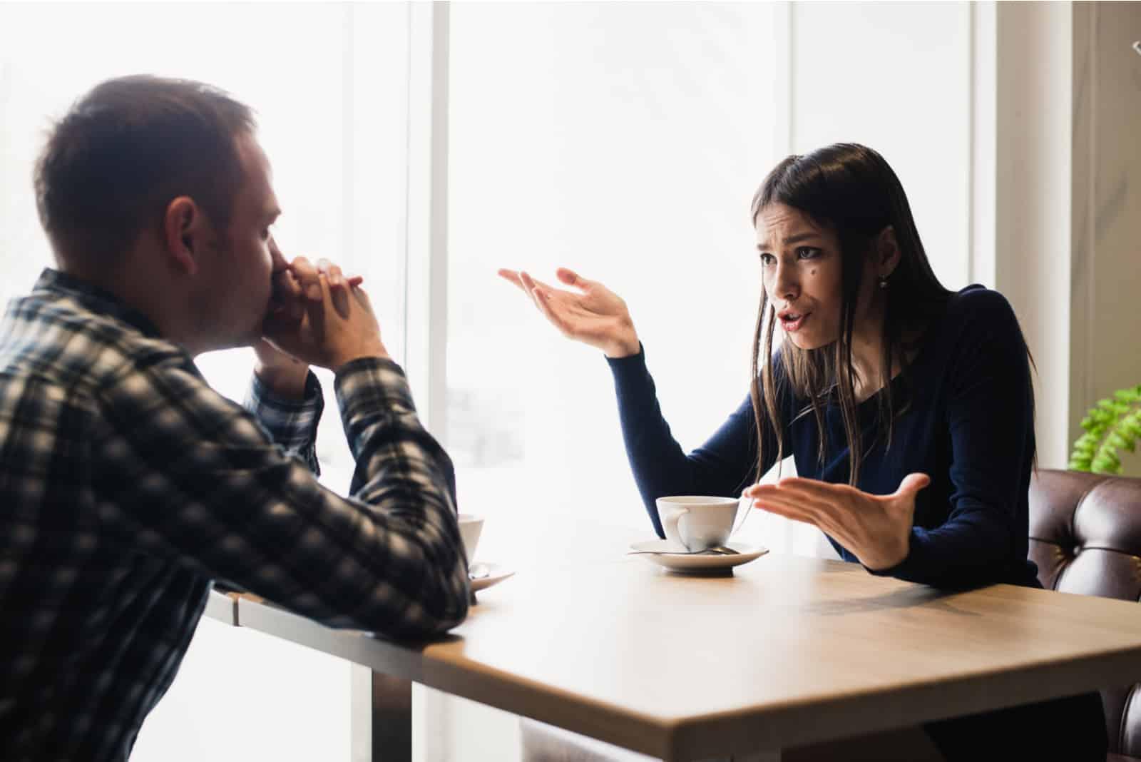 Ein Mann und eine Frau sitzen in einem Café und streiten sich