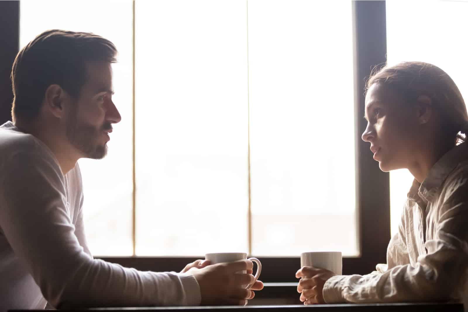Ein Mann und eine Frau unterhalten sich in einem Café