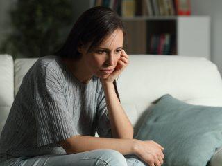 nachdenkliche Frau in der Nacht auf einer Couch sitzen