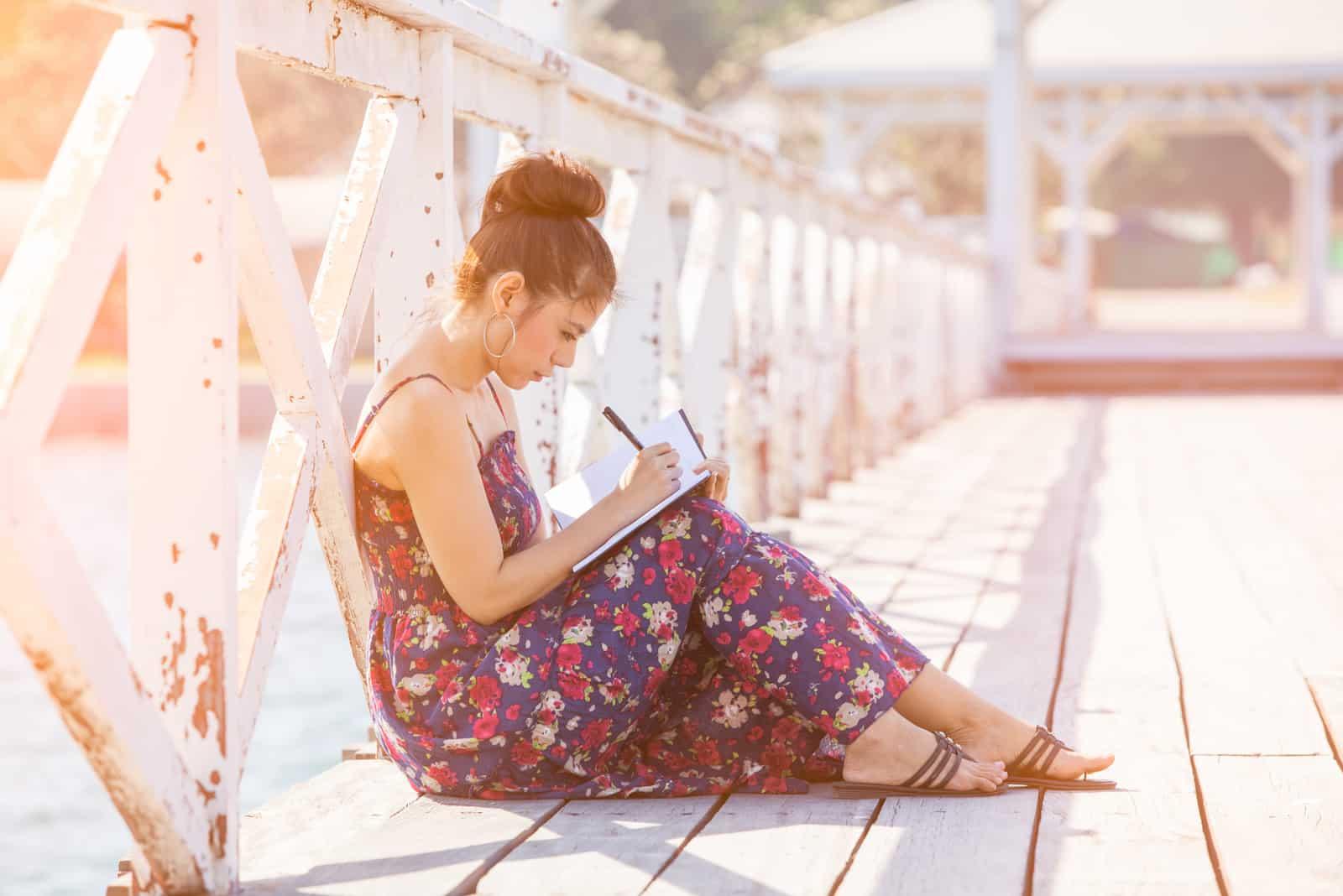 Eine Frau sitzt auf einer Brücke und schreibt