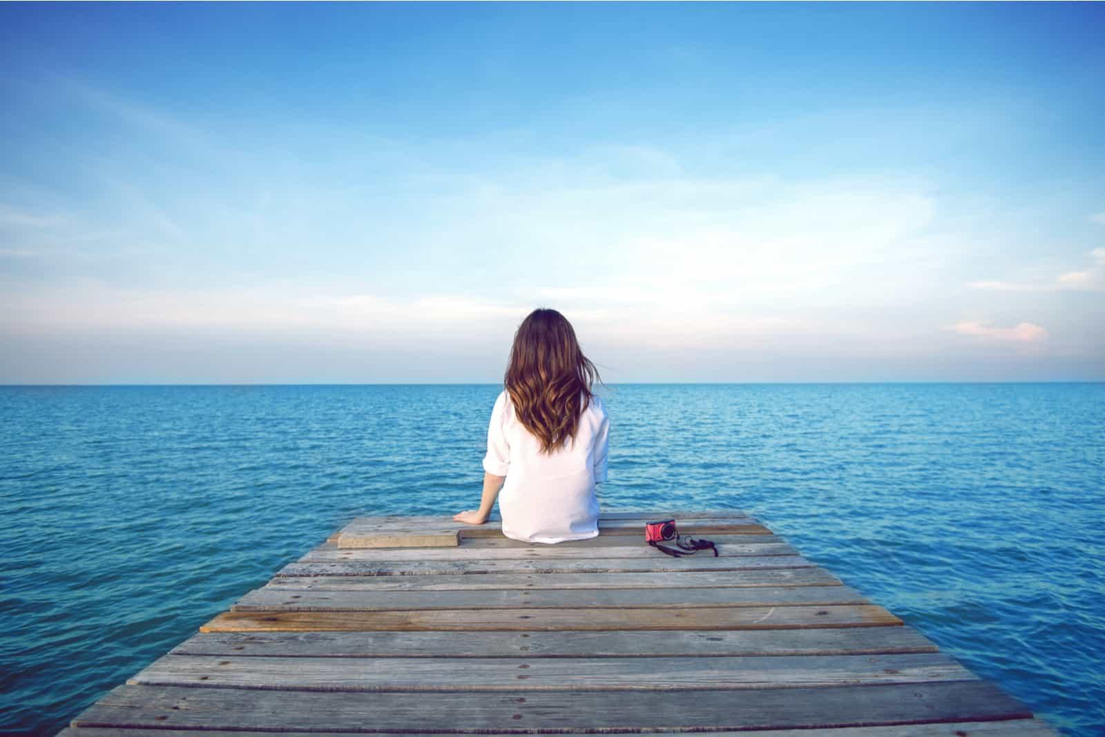 Eine imaginäre Frau sitzt auf einem Pier und schaut auf das Meer
