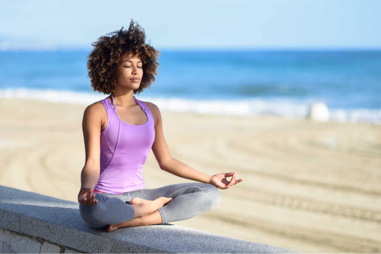 Frau, die Yoga Asana im Strand mit geschlossenen Augen tut