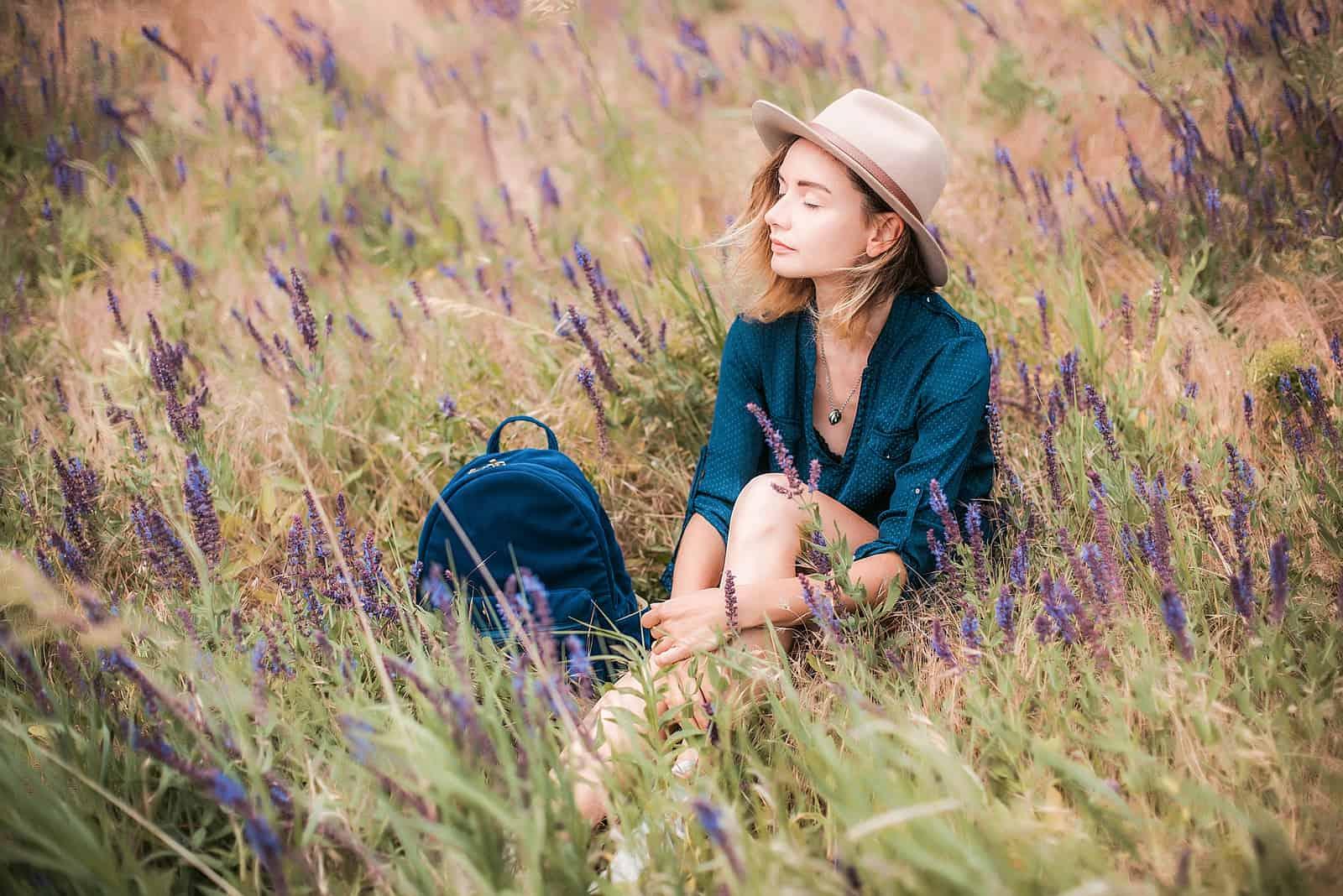 Frau, die in einem Gras am sonnigen Tag sitzt