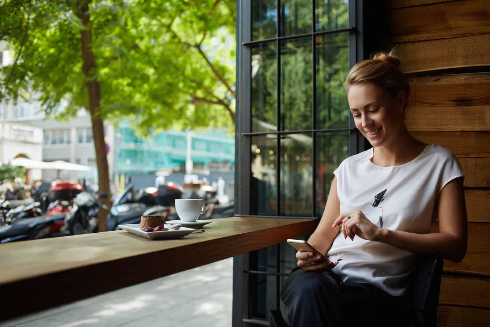 Frau mit schönem Lächeln liest gute Nachrichten auf dem Handy