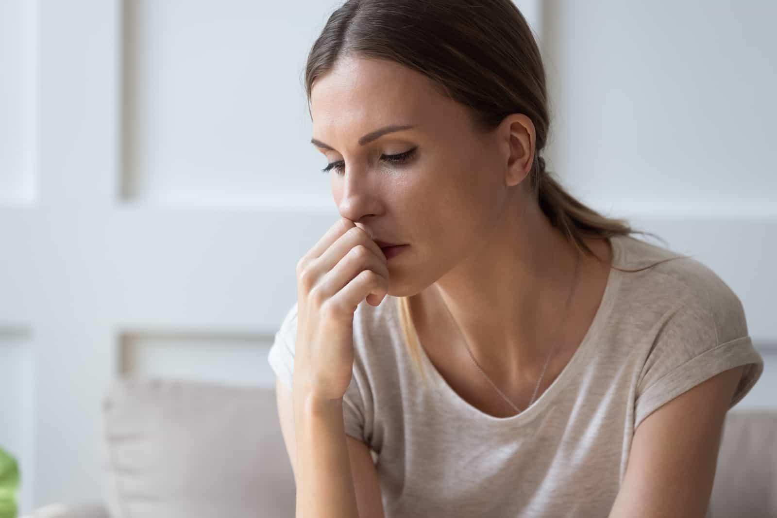 Frau sitzt alleine und denkt über persönliche Probleme in Beziehungen nach