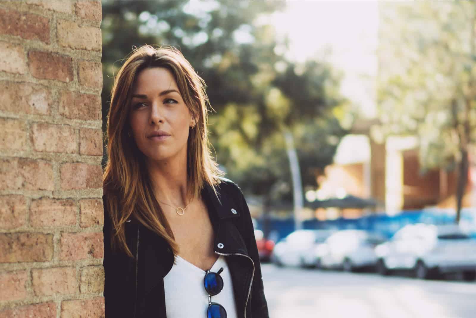 Frau steht auf einer Straße an einer Mauer gelehnt