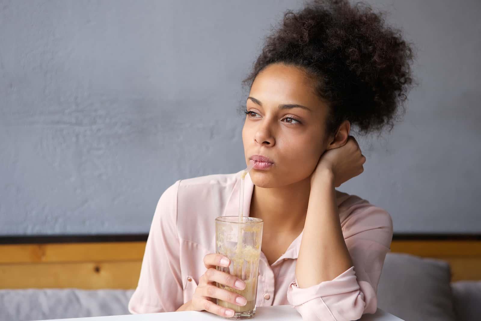 nachdenkliche Frau, die Milchshake trinkt