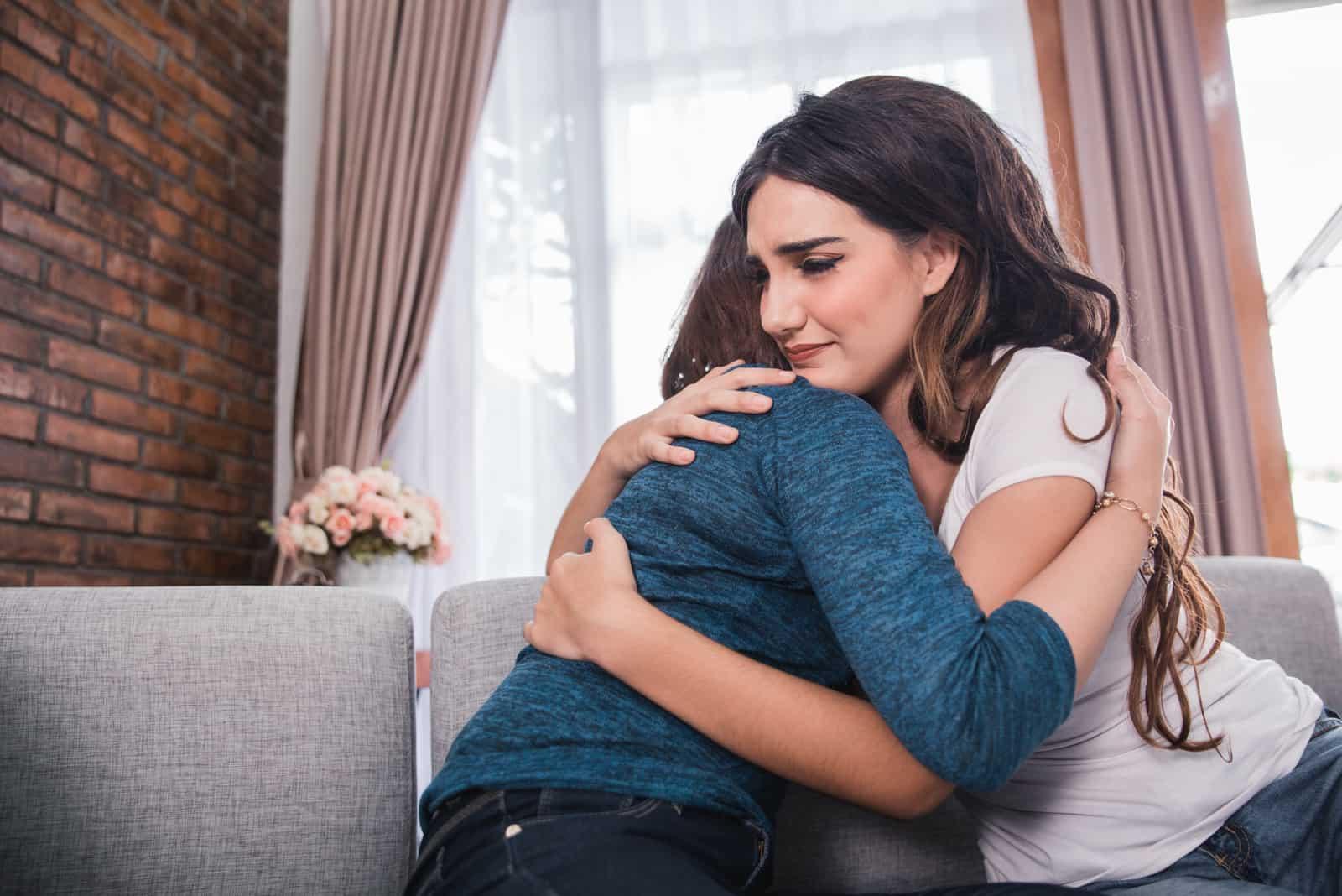Freundin beruhigt ihre Freundin durch Umarmung und Umarmung