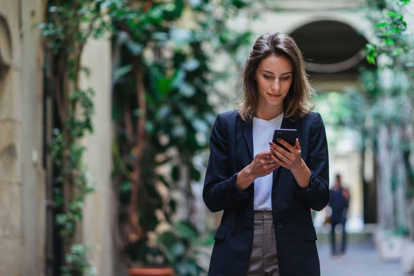 Geschäftsfrau, die auf Handy im Freien verwendet