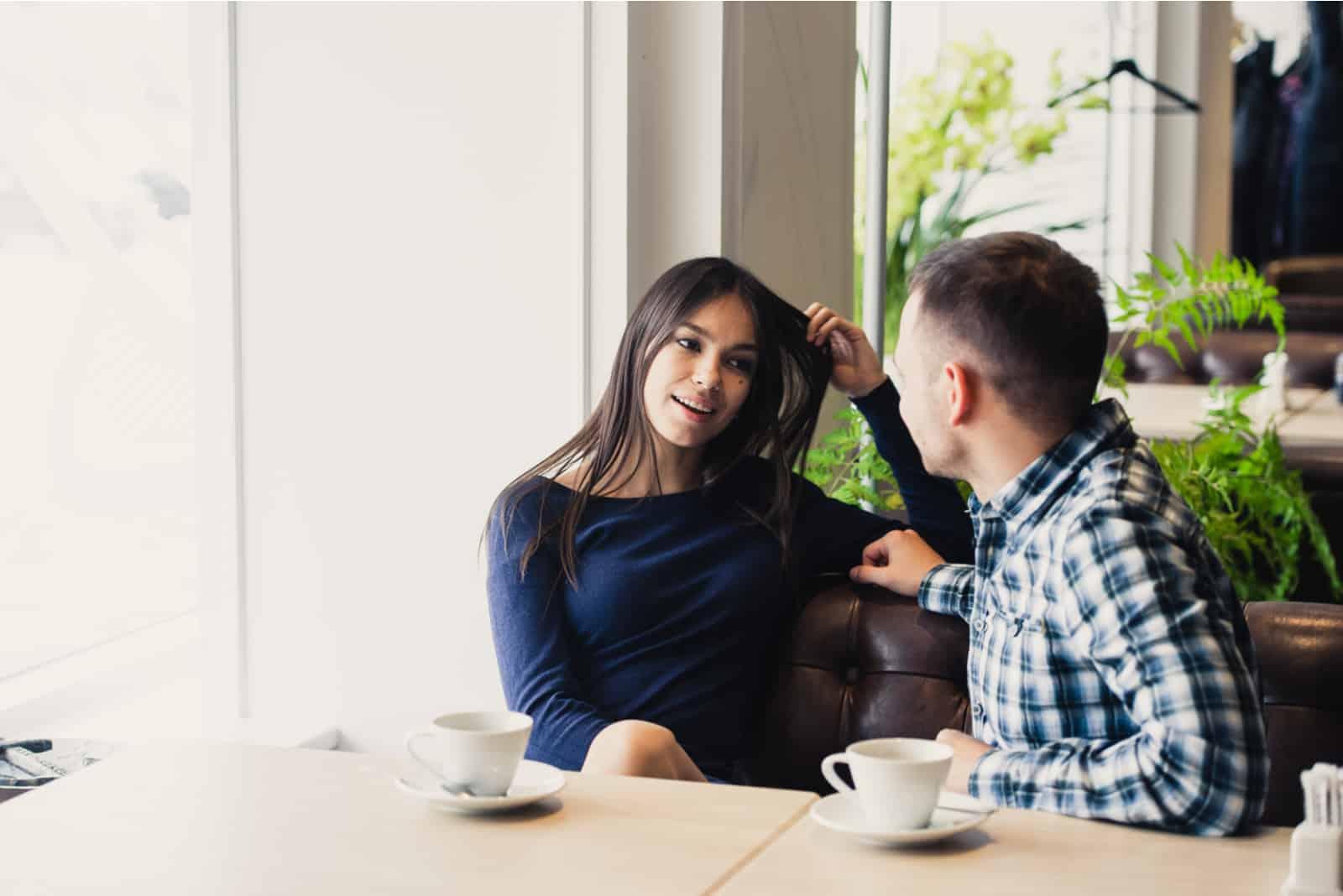 Glückliches Paar, das im Café spricht