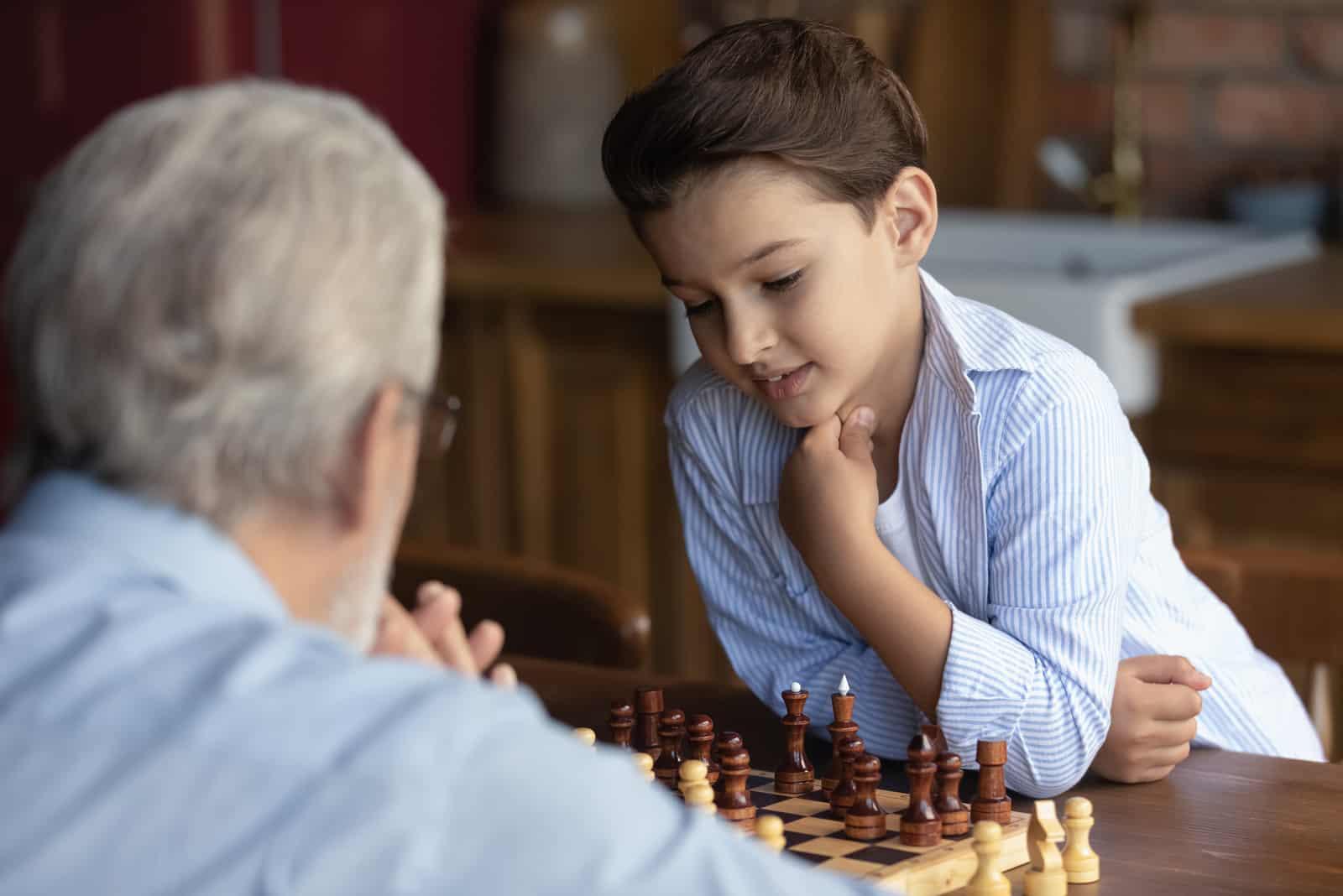 Junge Kind spielen Schach mit alten 60er grauhaarigen Großvater