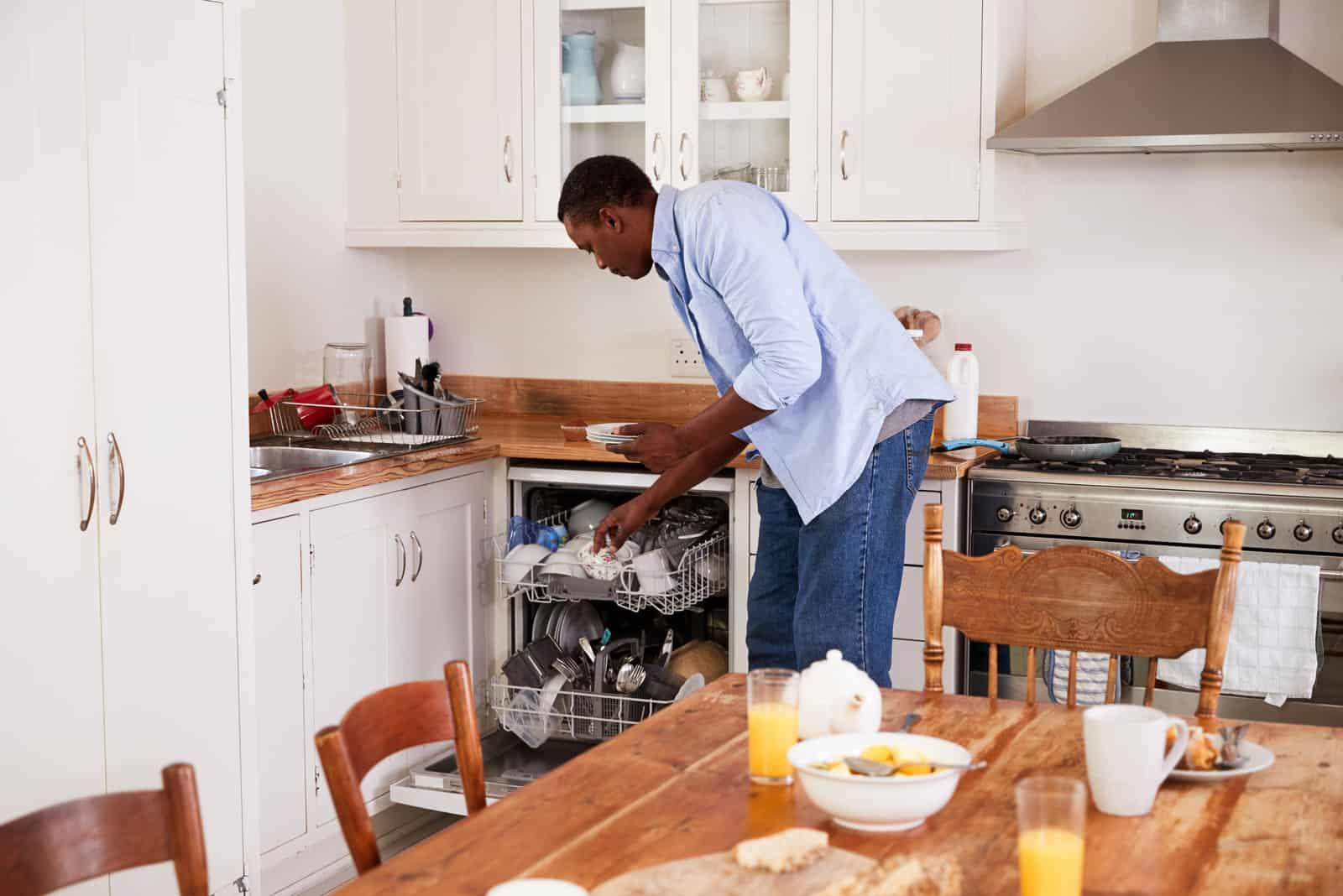 Mann, der Frühstückstisch löscht und Geschirrspüler lädt