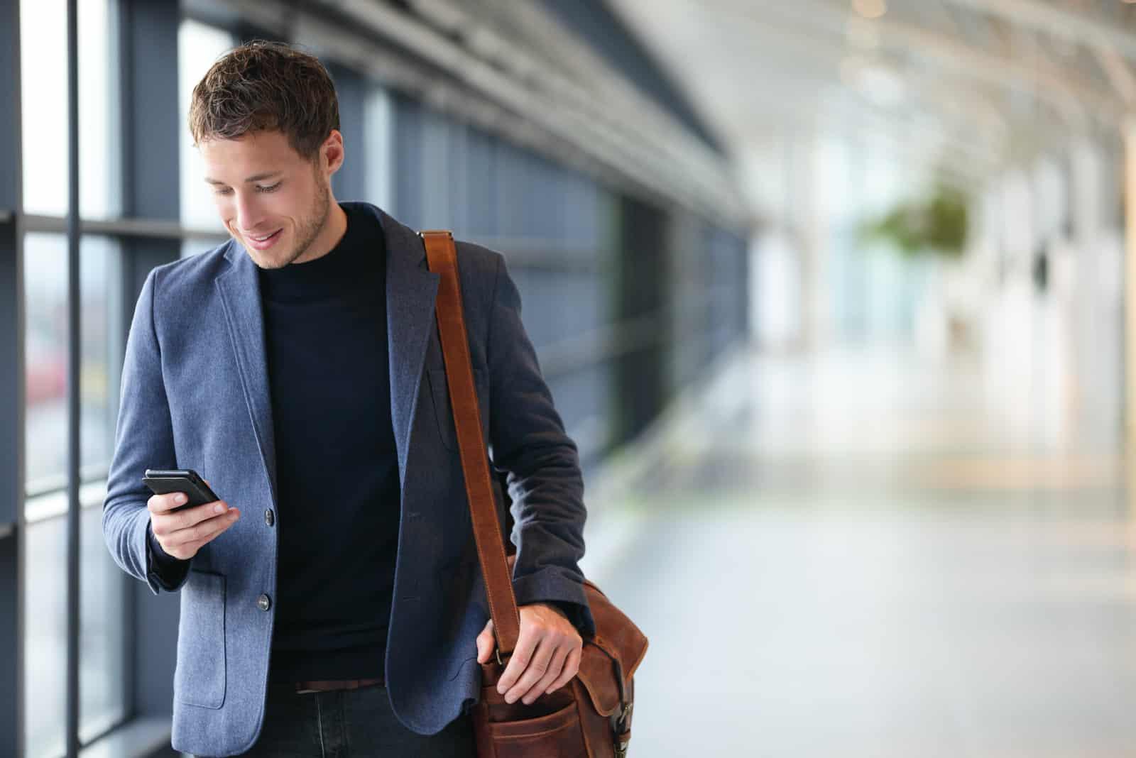 Mann hält Telefon lächelnd