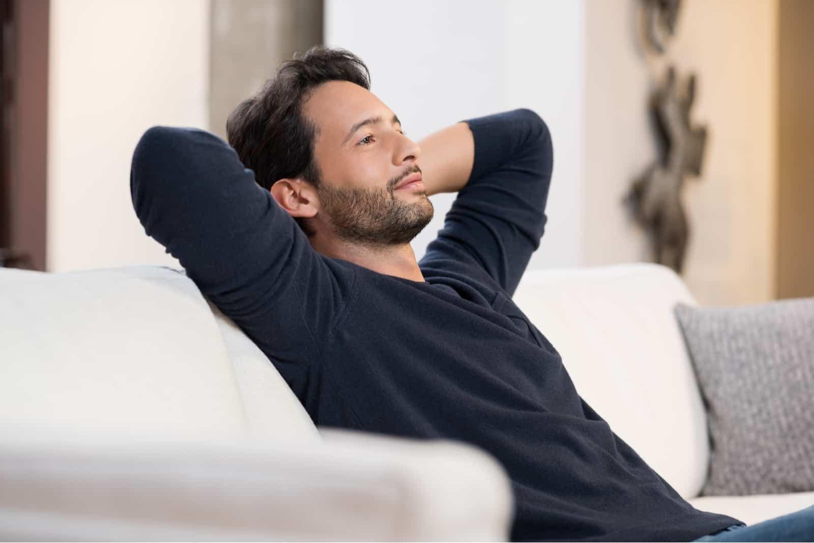 Mann ruht auf Sofa und denkt nach
