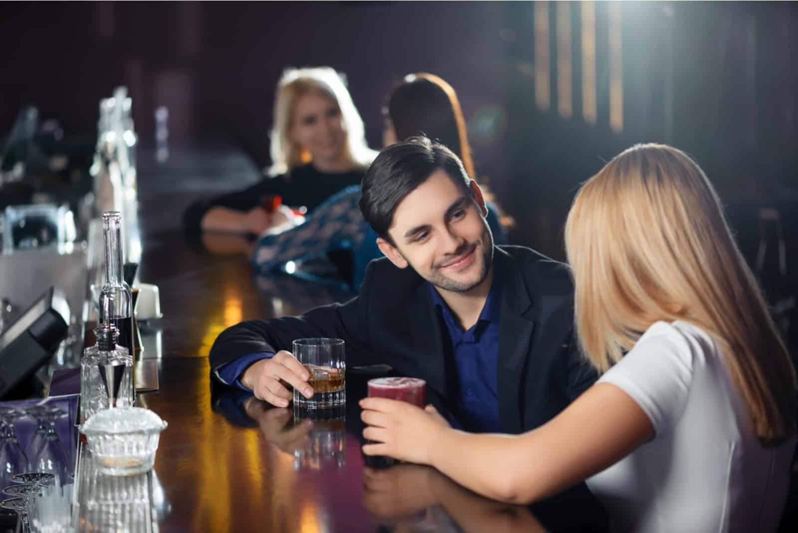 Paar, das freudig an der Bartheke im Nachtclub interagiert