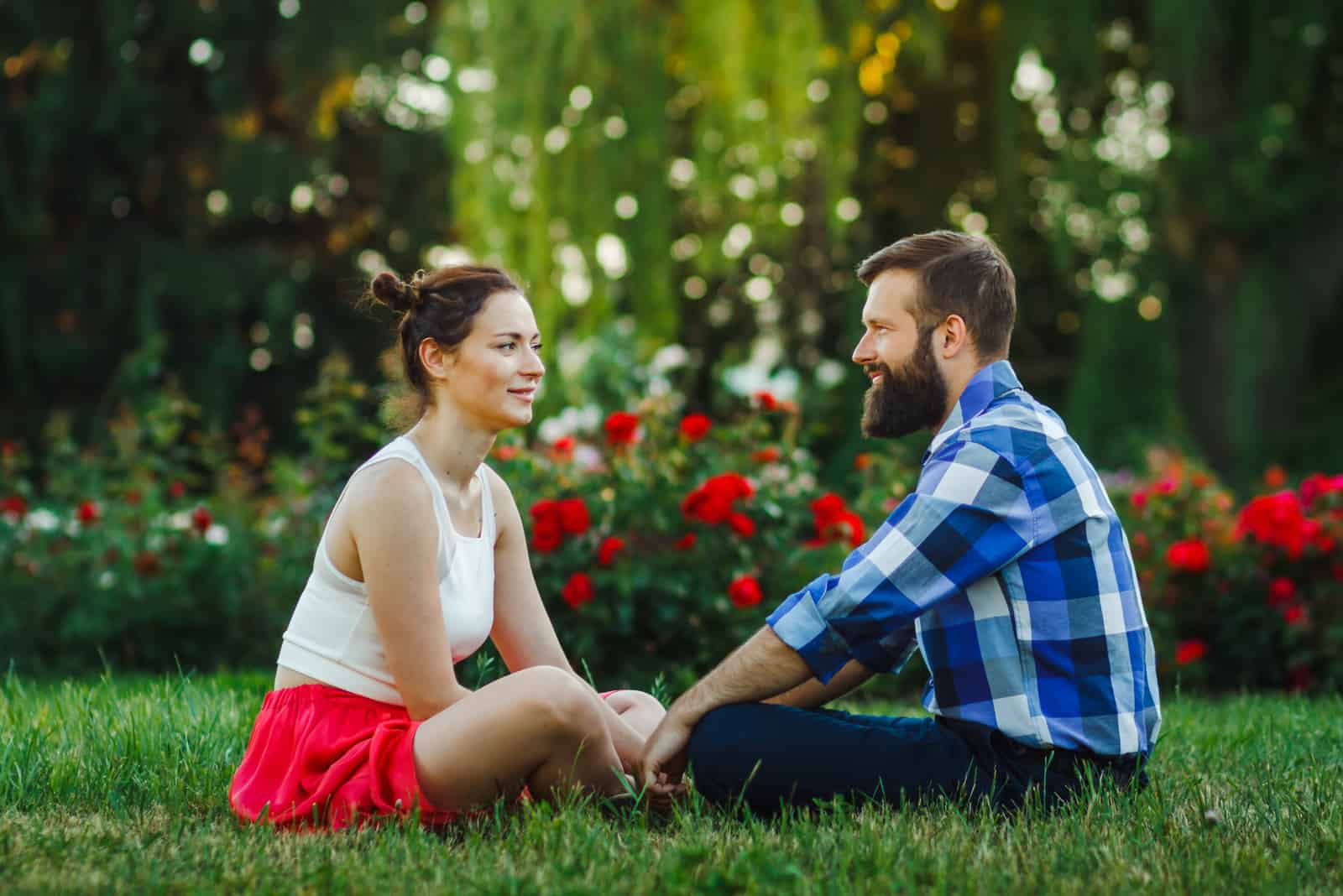 Paar im Freien miteinander reden - auf Gras sitzen