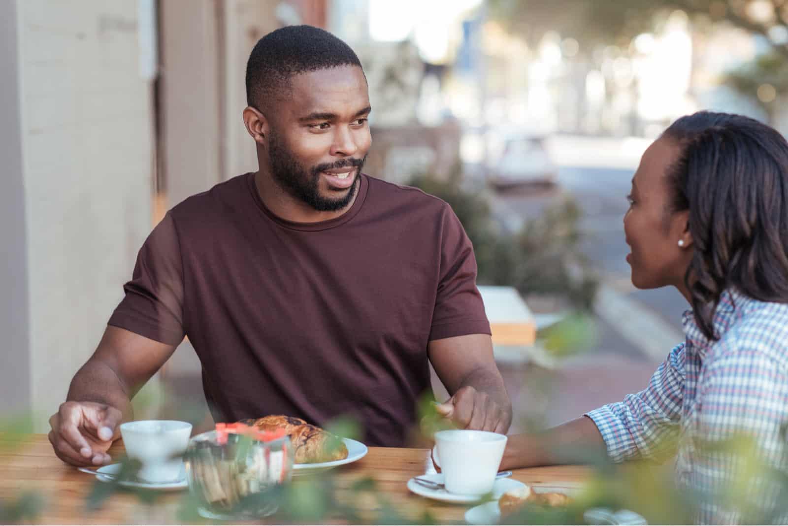 Paar sitzt an einem Tisch in einem Straßencafé und trinkt Kaffee