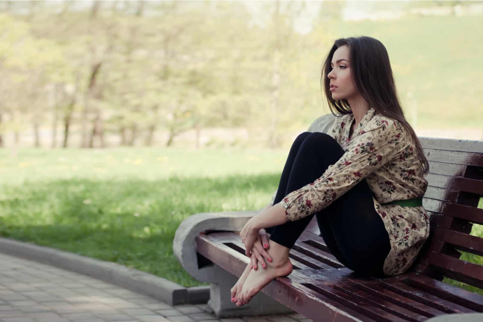 Schönes Mädchen, das auf der Bank sitzt