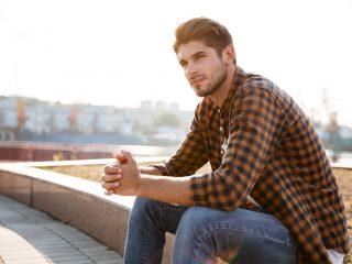 Mann im karierten Hemd, der draußen sitzt und denkt