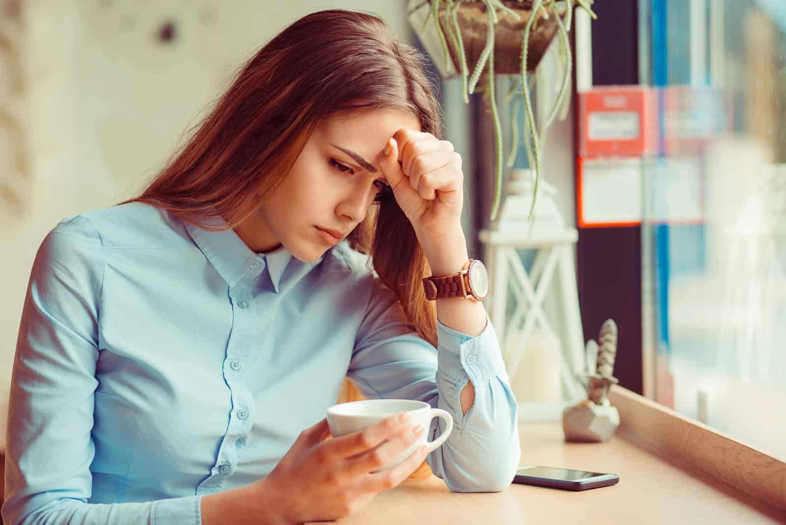 eine enttäuschte Frau, die in einem Café sitzt