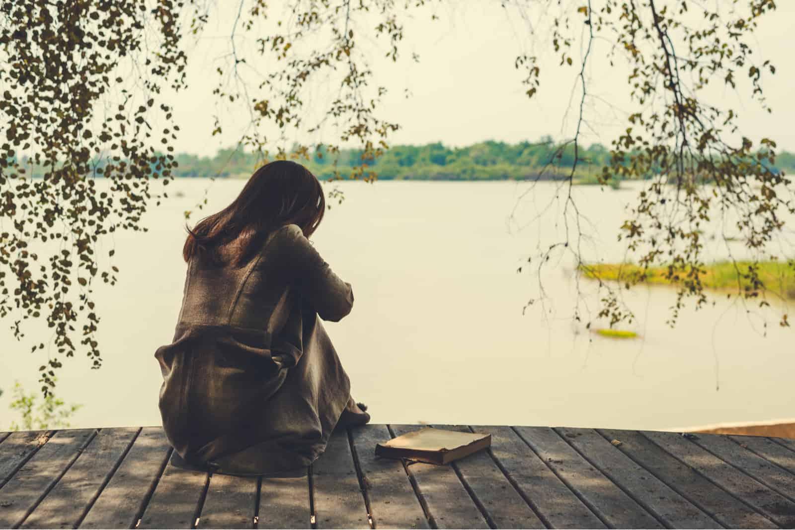 eine traurige Frau, die auf dem Pier sitzt