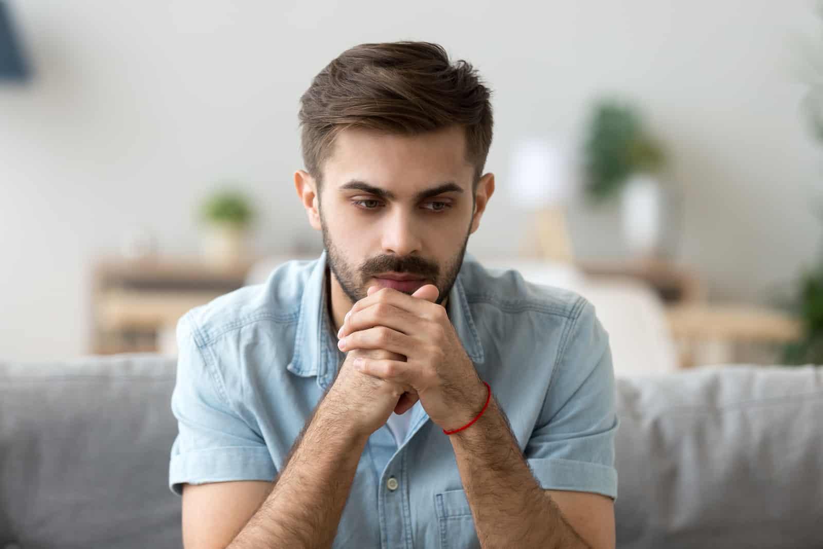 ernster Mann, der auf Couch nach Hause sitzt