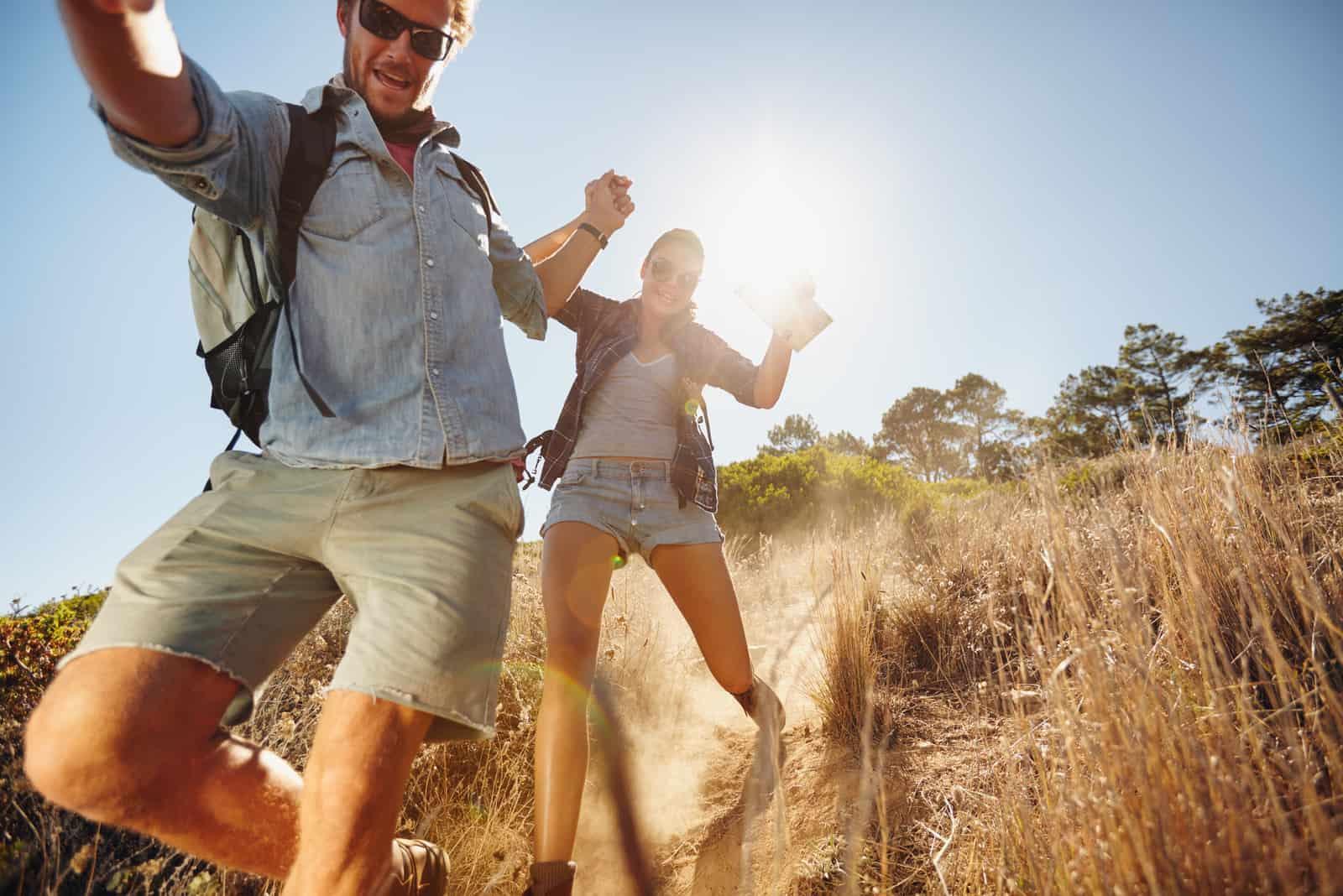 glückliches junges Paar, das Spaß auf ihrer Wanderung hat