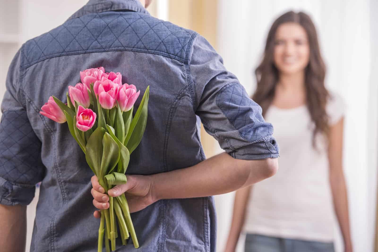 junger Mann versteckt Blumen hinter dem Rücken