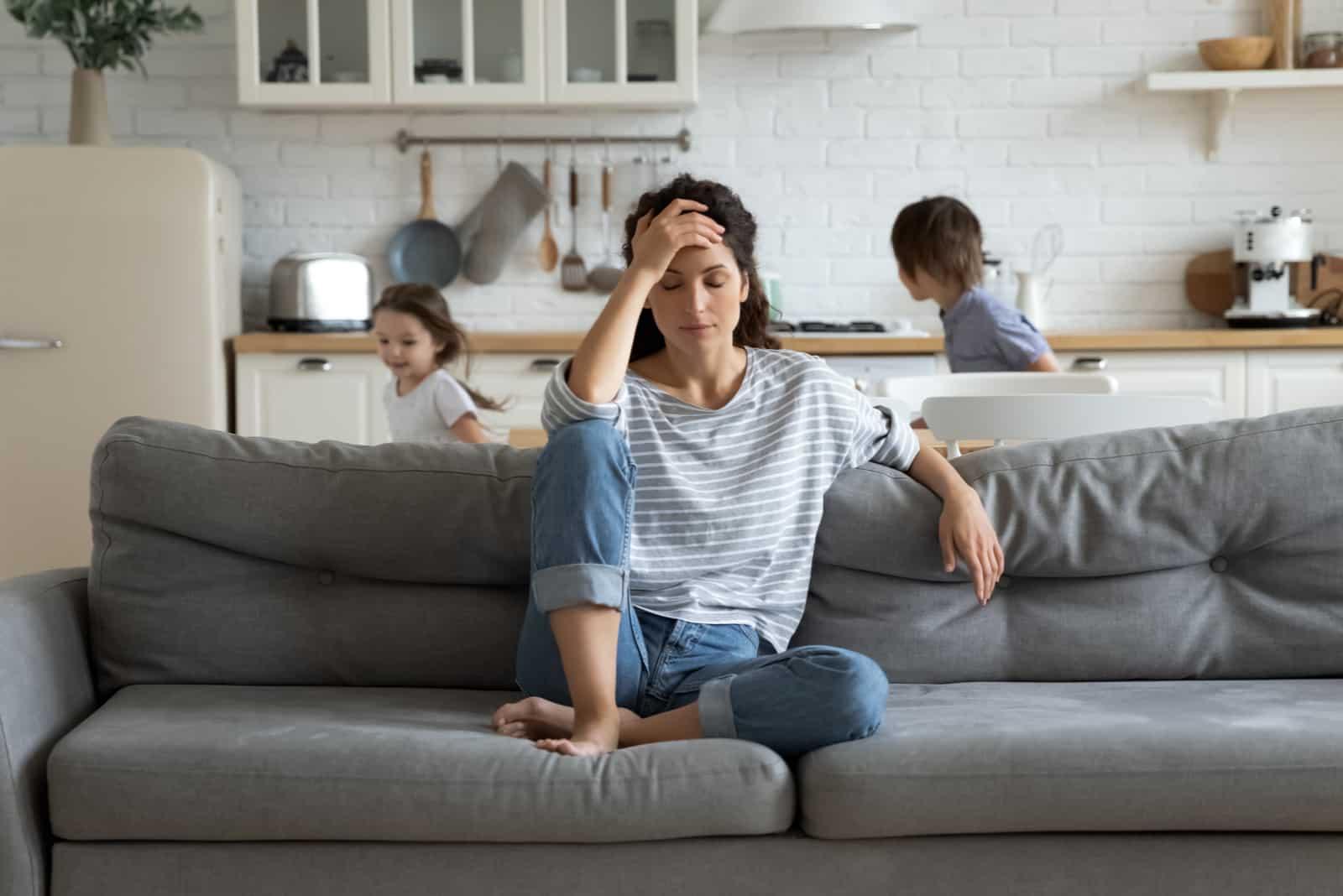 müde alleinerziehende Mutter leidet unter Kopfschmerzen