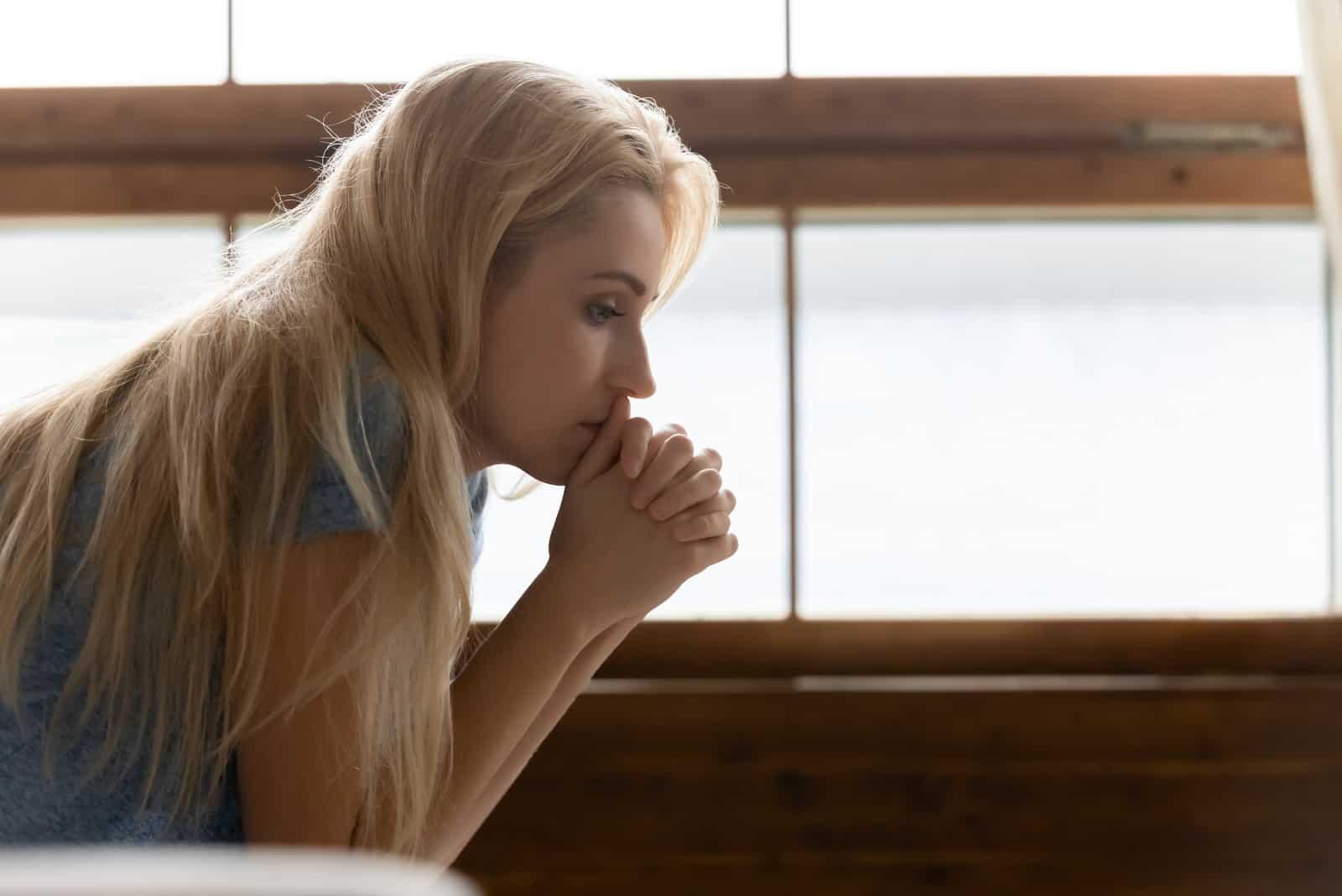 nachdenkliche nachdenkliche traurige junge Frau, die drinnen sitzt