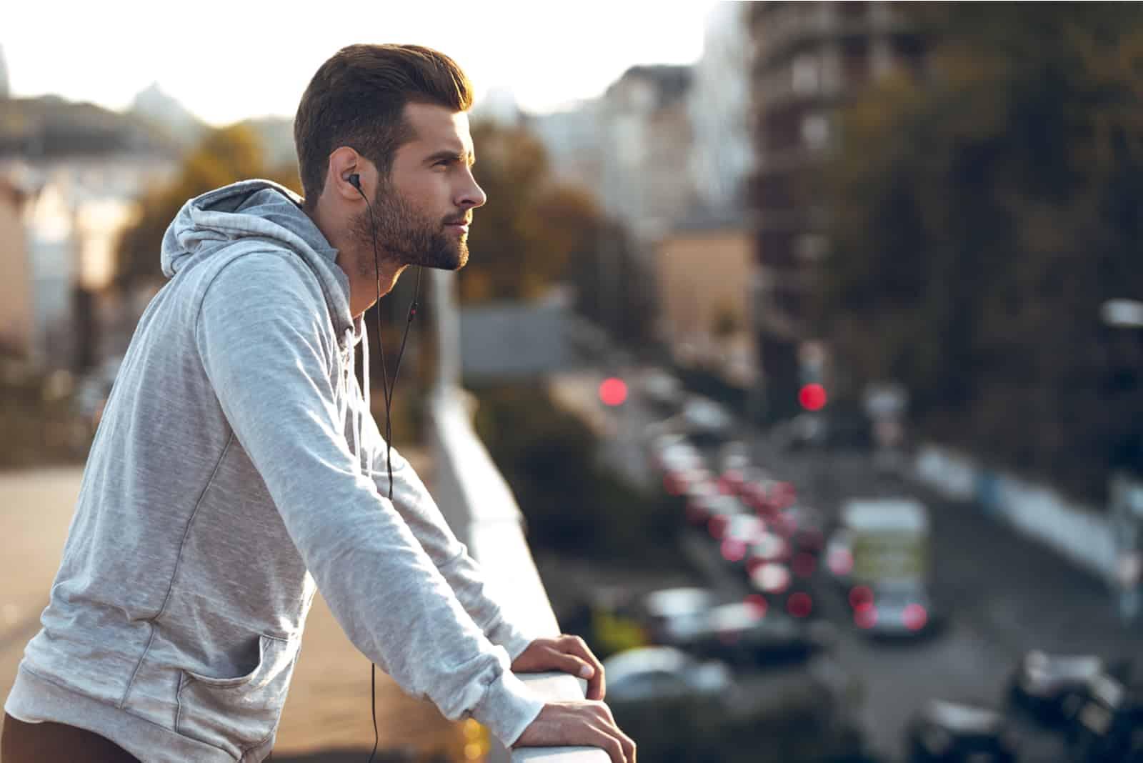 nachdenklicher junger Mann, der Kopfhörer trägt und wegschaut