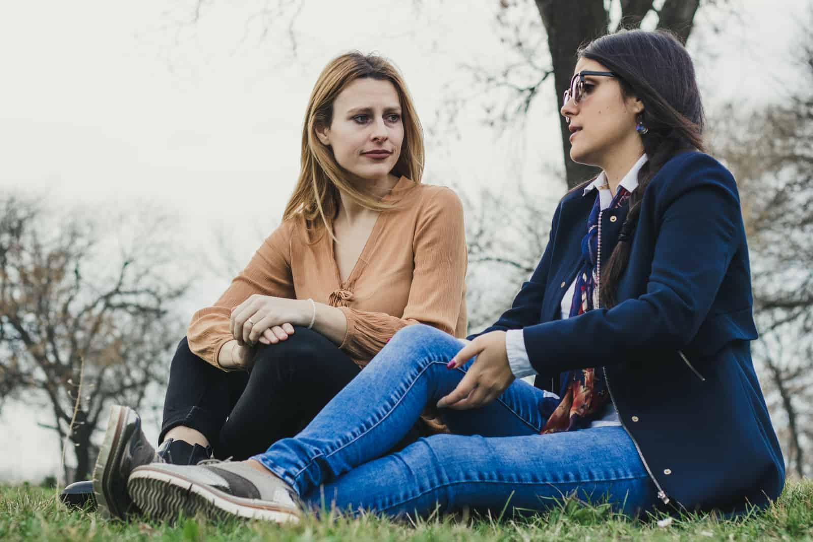 zwei Freunde, die auf Gras sitzen und reden