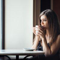 Schöne junge Frau mit einer Tasse Tee in einem Café