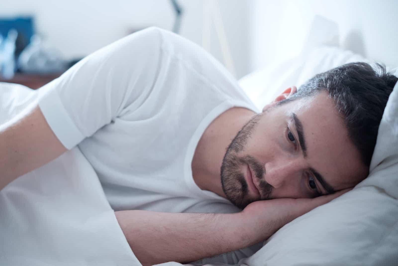 Depressiver Mann, der in seinem Bett liegt und sich schlecht fühlt