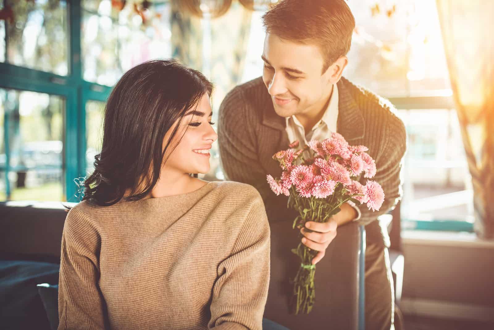 Der glückliche Mann, der im Restaurant Blumen für eine Frau schenkt