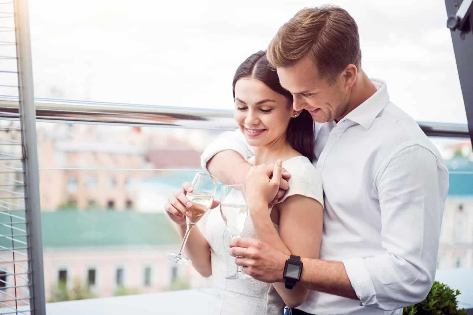 Ein Mann umarmte eine Frau, die mit einem Glas Wein anstieß