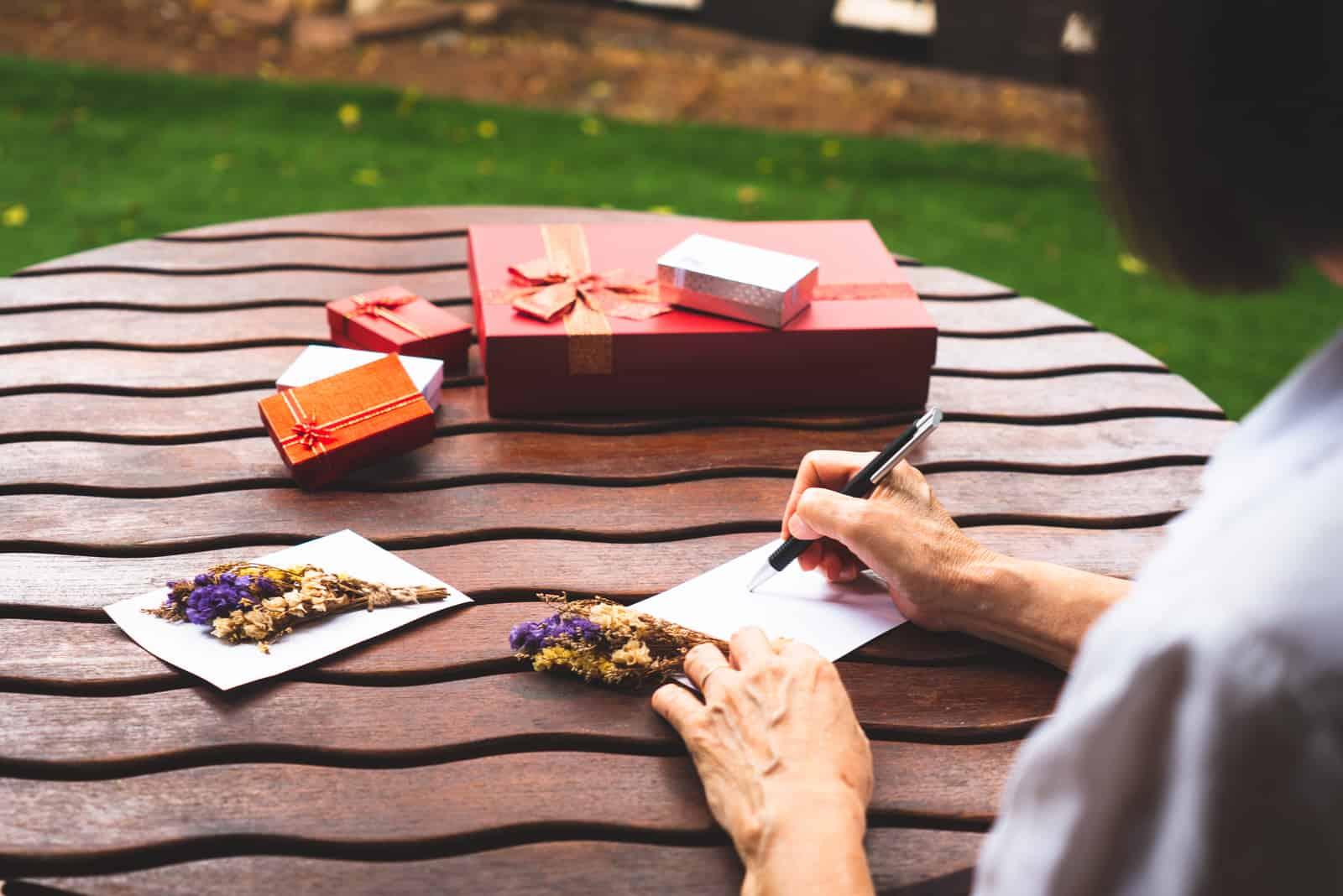 Eine Frau, die an einem Tisch sitzt, schreibt eine Grußkarte