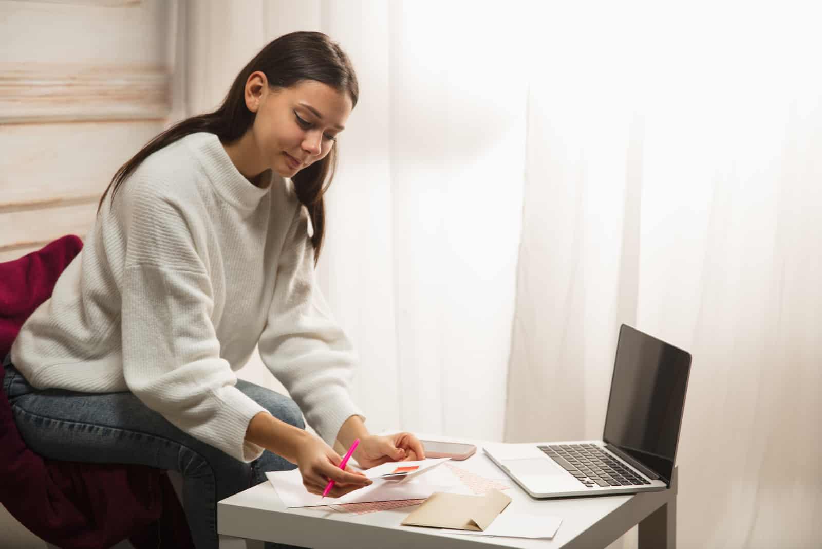 Eine schöne Frau mit langen schwarzen Haaren schreibt eine Grußkarte