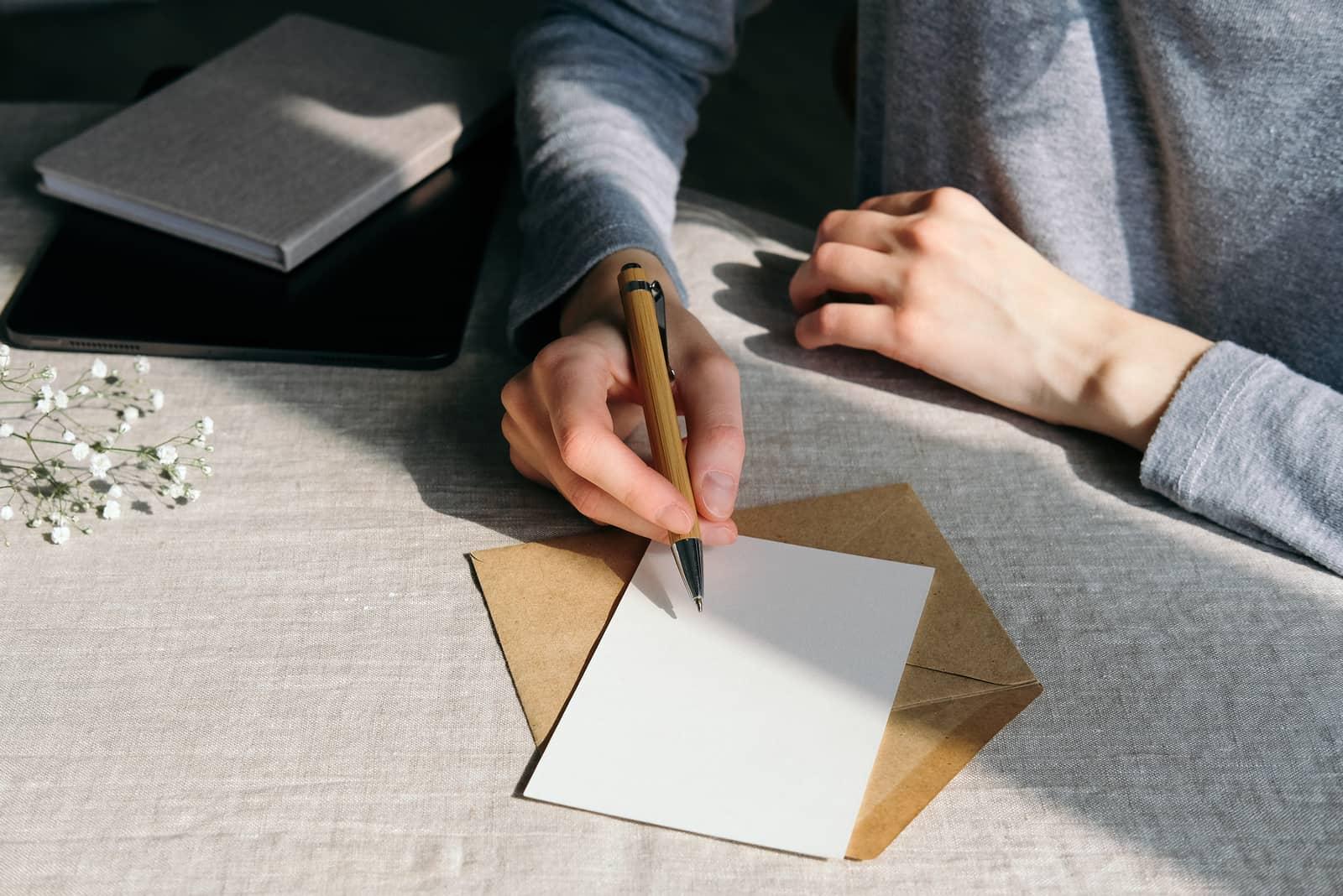 Eine schöne Frau schreibt eine Grußkarte