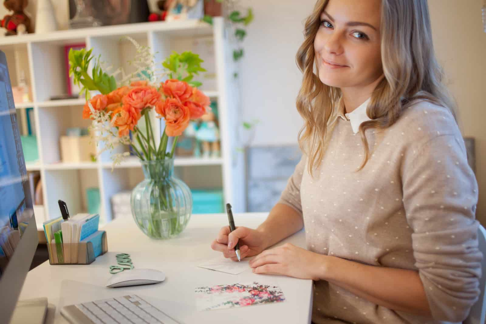 Eine schöne blonde Frau sitzt und schreibt eine Grußkarte