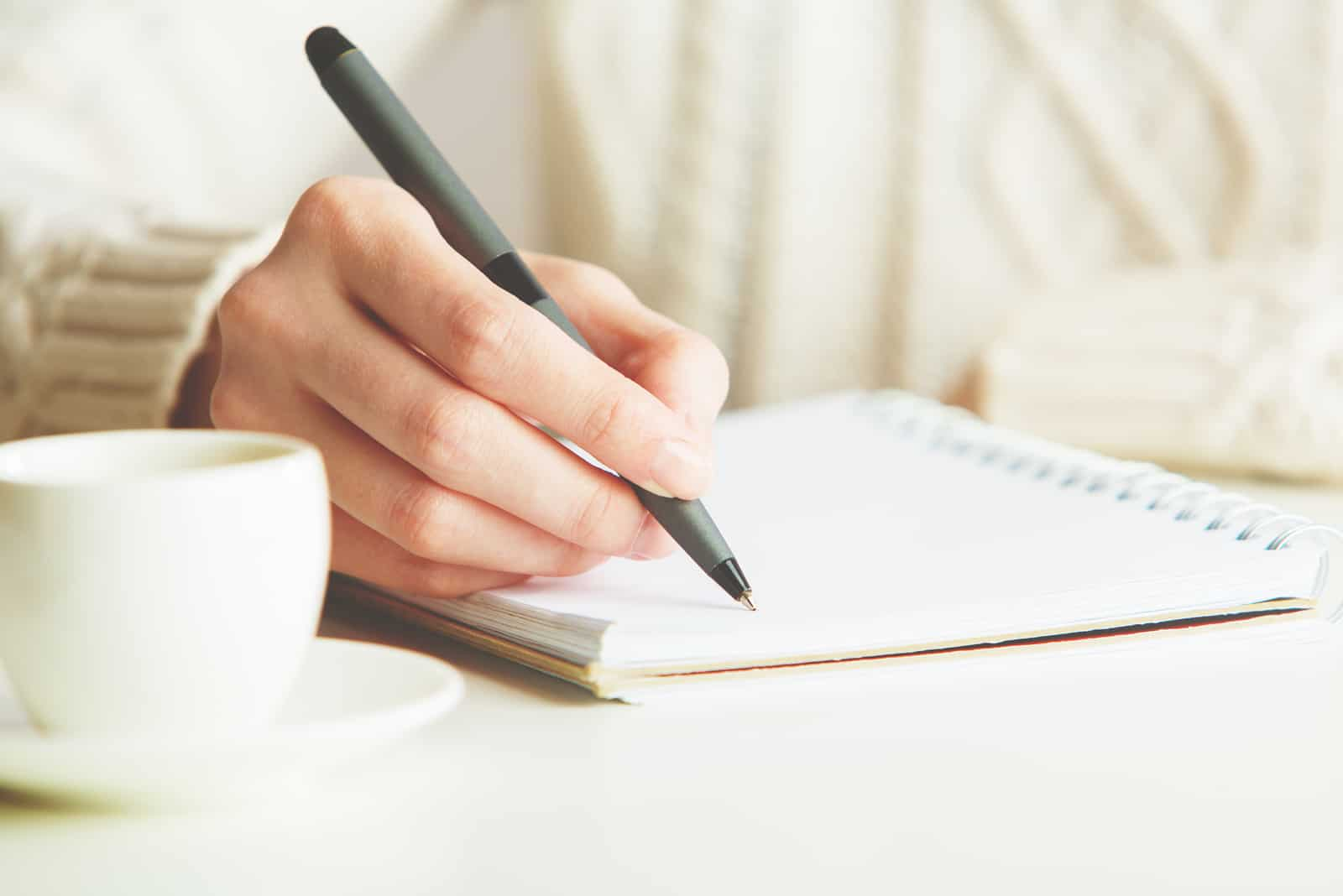 Frau, die im Spiralblock schreibt, der auf hellem Schreibtisch platziert wird
