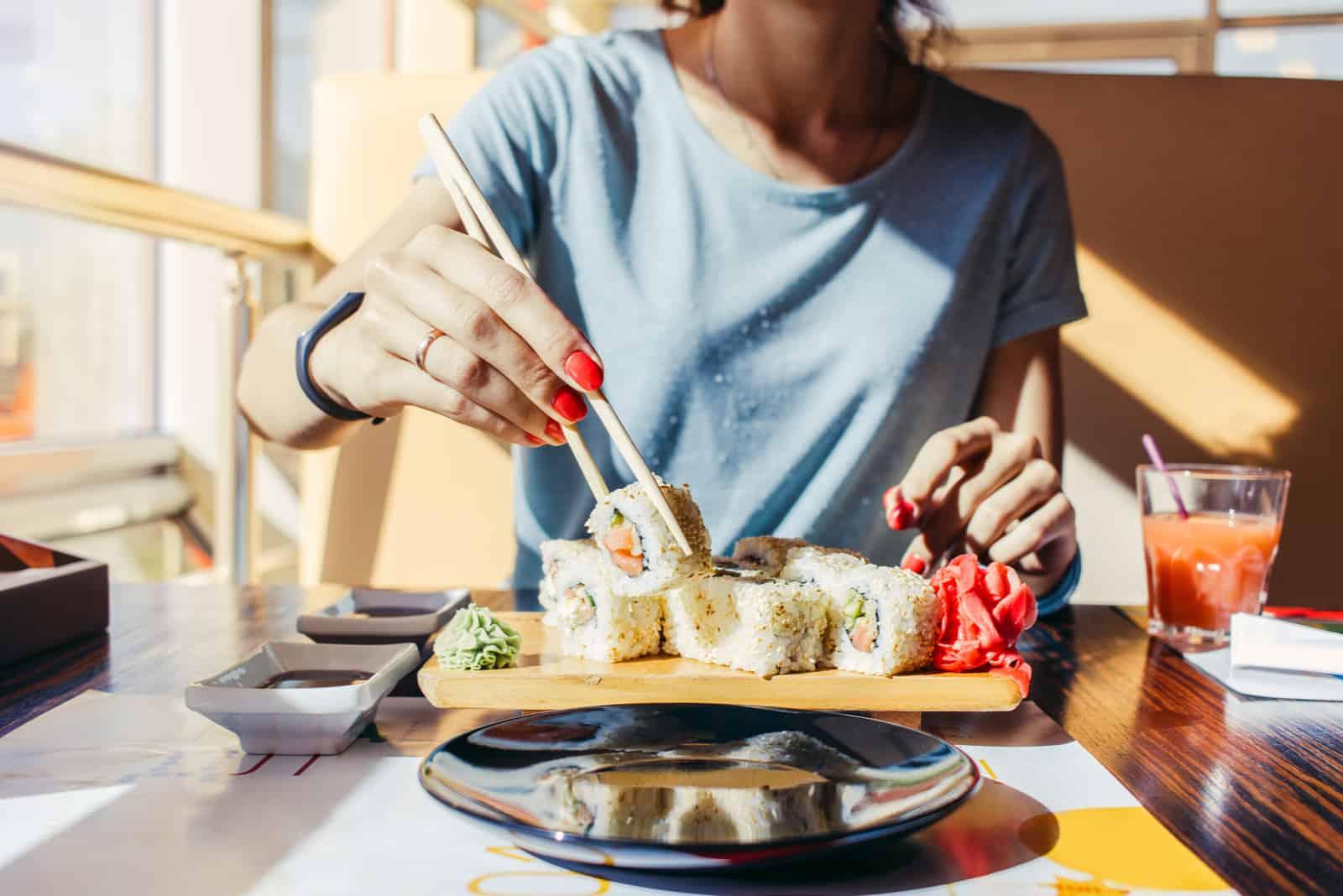 Frau im blauen Hemd isst an einem Sushi-Restaurant
