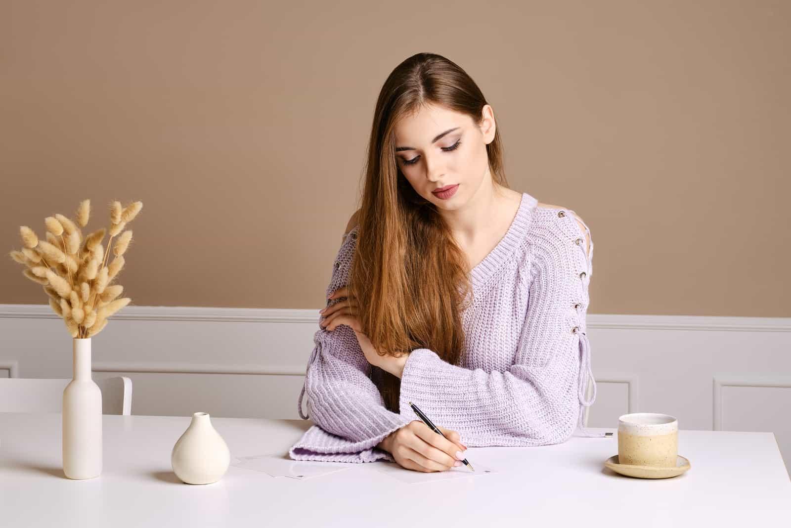 Frau mit langen braunen Haaren sitzt am Tisch und schreibt Gruß