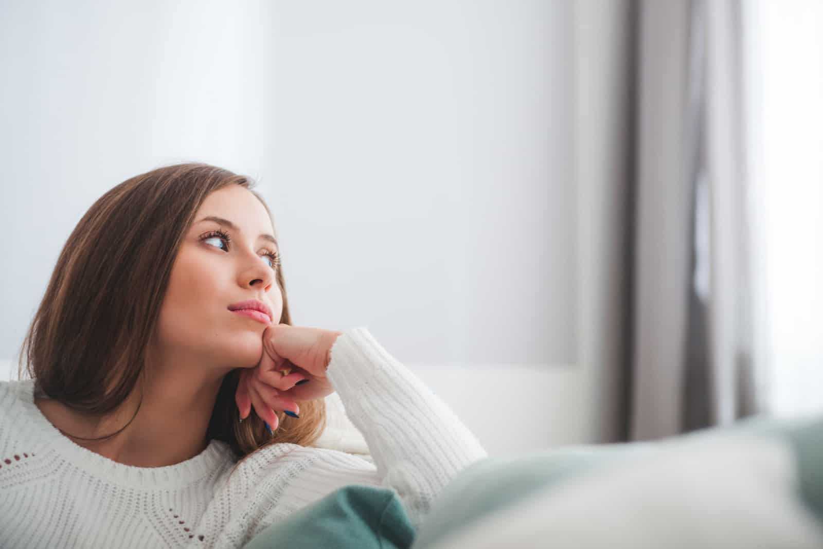 Frau sitzt auf dem Sofa zu Hause tief in Gedanken