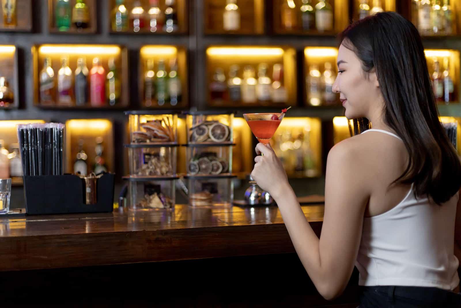 Frau sitzt in der Bar und trinkt