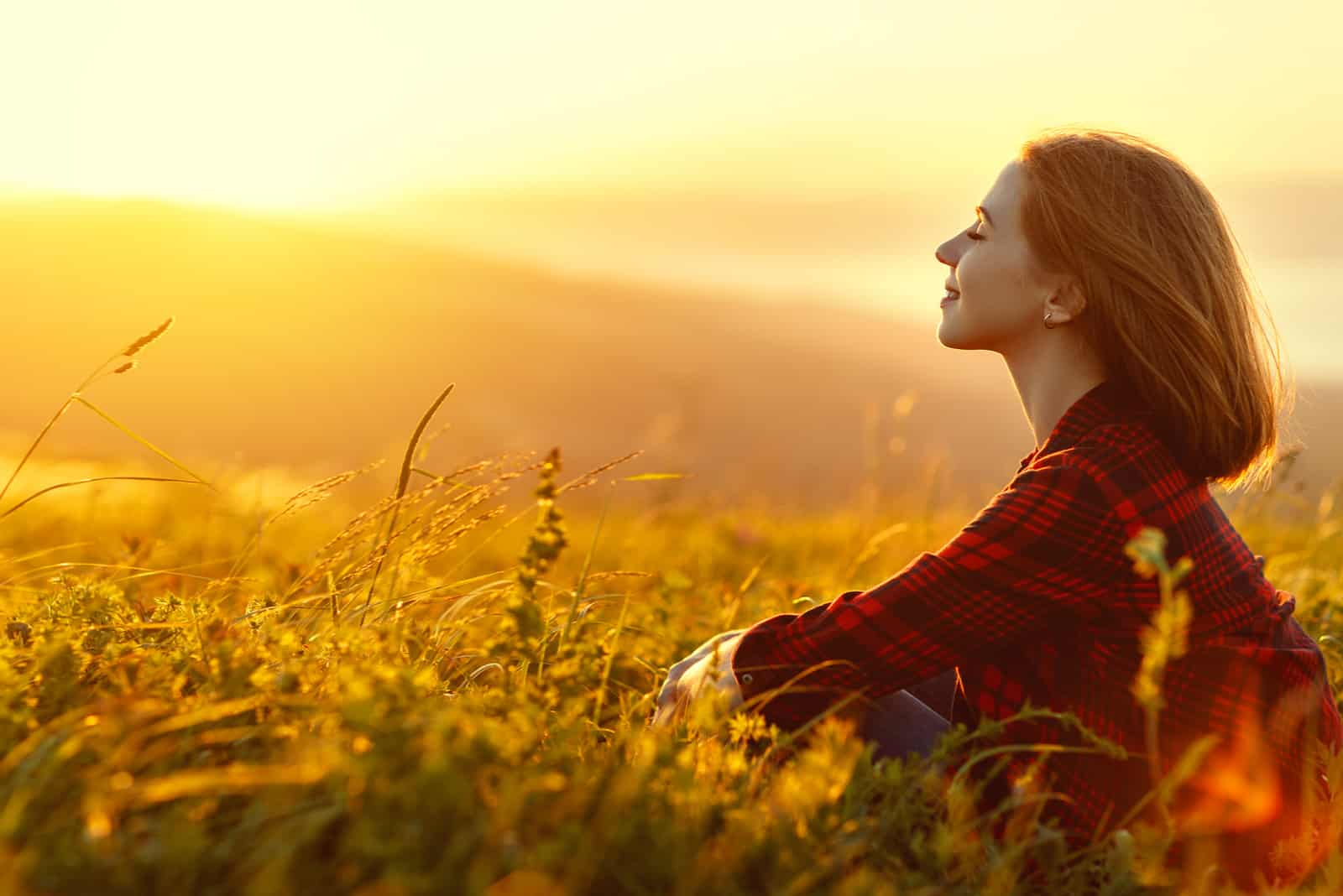 Frau sitzt mit dem Rücken auf dem Feld und bewundert den Sonnenuntergang
