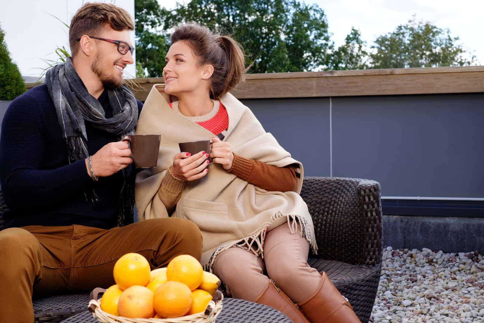 Fröhliches Paar auf einer Terrasse am Herbsttag