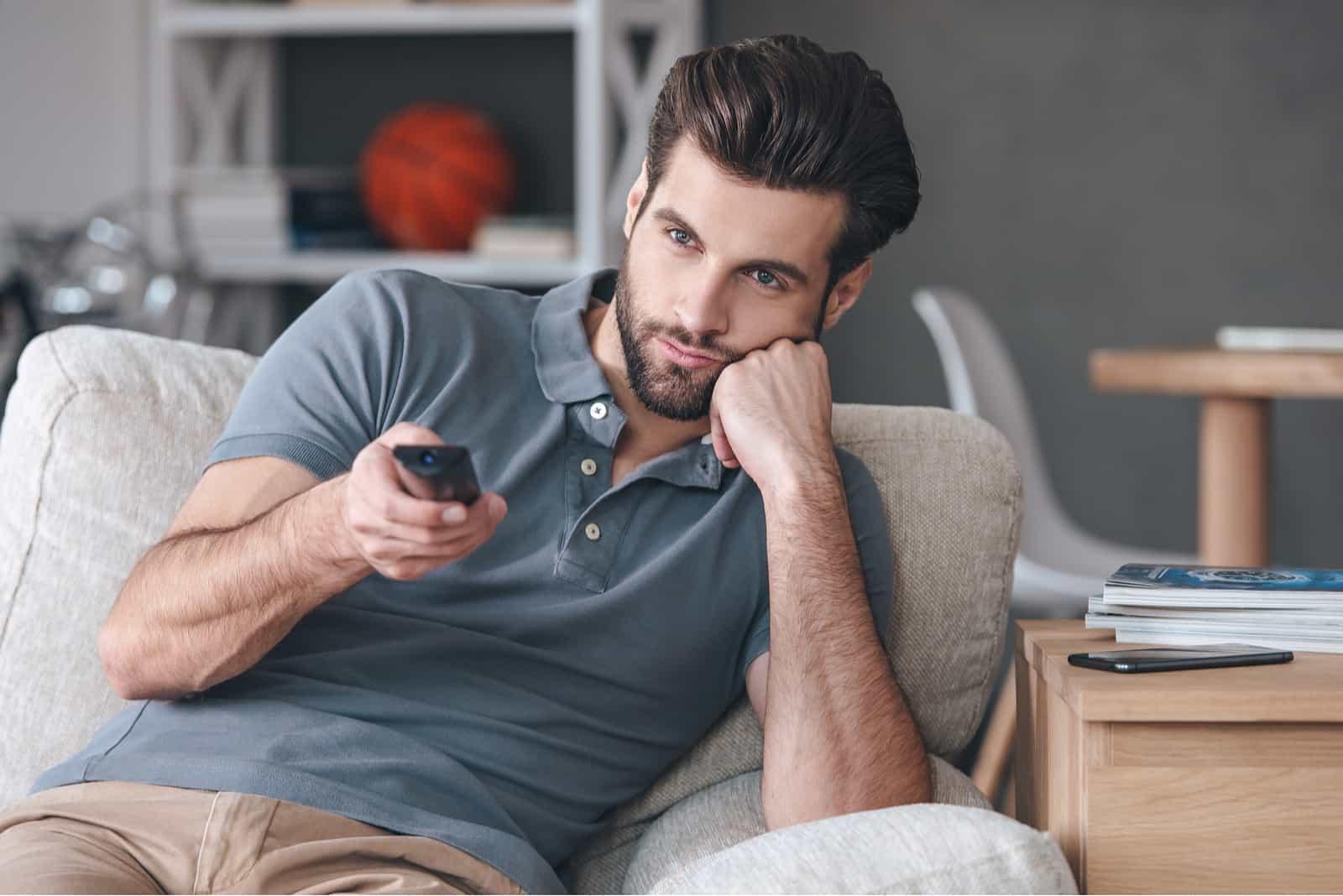 Hübscher junger Mann, der Fernbedienung hält und gelangweilt beim Fernsehen schaut