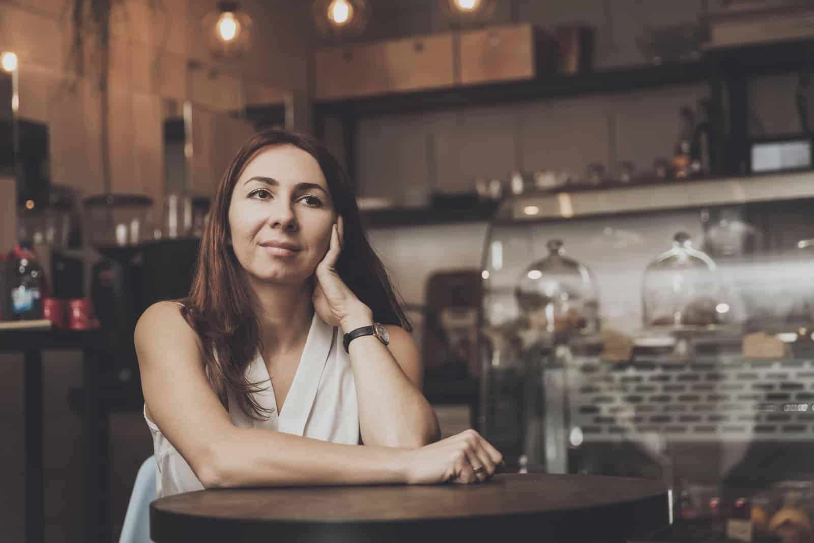 Mädchen sitzt in einem Café und wartet auf einen jungen Mann